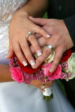 The rings. Bride and groom's hands on bouquet Stock Photos