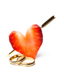 Rings and arrow. Strawberry pierced by cupid's arrow, and wedding rings Royalty Free Stock Images