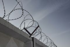Restriction of freedom, bondage. Rings of barbed wire on top of a concrete fence, in the background sky. Prison zone, forbidden territory, punishment for a Stock Photography