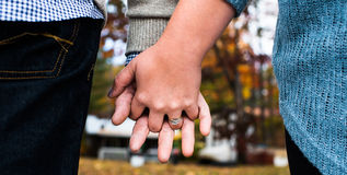 With these rings, we begin our lives together. A young couple contemplate their lives together while holding hands Royalty Free Stock Photos