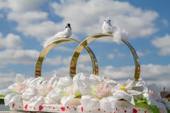 Rings with birds on a background cloudy sky. Wedding decorations for the car Stock Photo