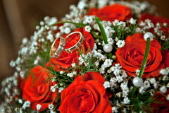 Rings bride and groom at the wedding bouquet of red roses.  Royalty Free Stock Image