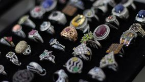 Rings with different precious stones, materials, sizes and shapes in the display of a jewelry stock photo