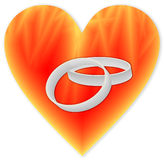 Rings in a fiery heart. Silver wedding rings in a fiery heart Stock Photography