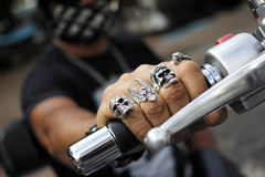Rings on fingers holding motorcycle Stock Image