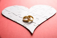 Rings on heart made of puzzle. Golden Rings On Heart Made Of Puzzle Over Orange Background Stock Photography