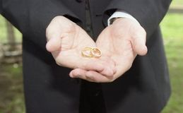 With these rings, I thee wed. Groomsman holding the two wedding rings in his hands Stock Photos
