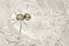 Rings on lace, heart-shaped pillow. Close-up of two rings on a white, heart-shaped pillow, with floral background Stock Image