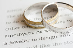 Rings of marriage. Two wedding bands rest on a page containing words about rings Royalty Free Stock Images