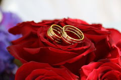 Rings for marriage. On bridal bouquets made with red roses stock image