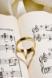 Rings and music. Wedding bands with heart shadow on sheet music stock image