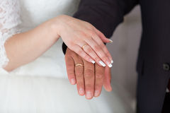 Rings newlyweds on their hands. Gold wedding rings on the hands of the newlyweds Stock Photography