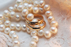 Rings and pearls. Two wedding rings with a pearl necklace Royalty Free Stock Photos