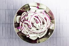 Rings of purple onions in a metal bowl. Fresh red onion on a light table royalty free stock images