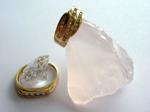 Rings, quartz and zircon. Gold diamond rings, zircon, and a large natural rose quartz Stock Photo