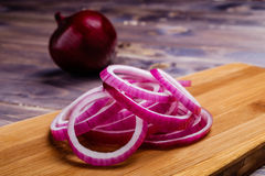 Rings of red onion. And knife on the board Stock Images