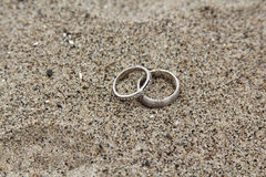 Rings in the Sand. His and hers wedding rings laying on a sandy beach Royalty Free Stock Photos