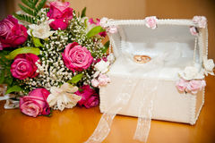 Rings in the trunk next to the wedding bouquet bride Royalty Free Stock Photography