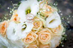 Rings on a wedding bouquet of white flowers and peach roses. Golden rings on a wedding bouquet of white flowers and peach roses Stock Image