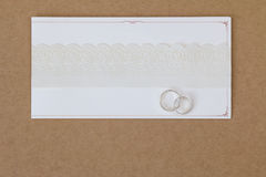 2 rings on a wedding invitation card with white paper lace ribbo Royalty Free Stock Image
