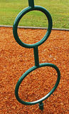 Rings, Wood Chips and Grass. Wet, green playground rings positioned in front of wood chips and grass Royalty Free Stock Images