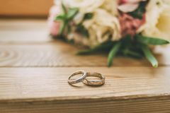 Rings on wooden floor with wedding flowers. Golden rings on wooden floor with wedding white and pink flowers Stock Image