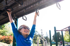On The Rings. A young girl plays on the rings at a park Royalty Free Stock Image