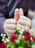 Ringson fingers painted with the bride and groom. Wedding rings on her fingers painted with the bride and groom stock image