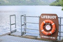 Ringwasser-Sicherheitsverhinderung des orange Rotes der Lebenboje, die szenisches Ansicht inversnaid Loch Lomond Schottland Großb Stockbild