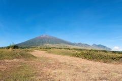Rinjani mountain and savannah field with blue clear sky.  Stock Photography