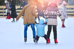Rink. Family on a skating rink. Fother and mother trains their son to skate. Family holding each other`s hands stock photography