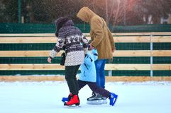 Rink. Family on a skating rink. Fother and mother trains their son to skate royalty free stock image