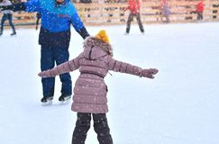 Rink. Father and daughter on a skating rink. Dad trains little daughter to skate on ice. Winter sports stock photos