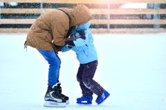 Rink. Father and son on a skating rink. Dad trains his son to skate. Winter sport hobby royalty free stock images
