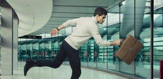 Rinnande affärsman med den bruna resväskan arkivfoton