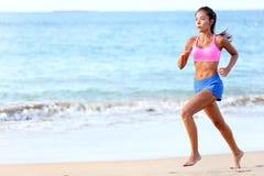 Rinnande beslutsam kvinnalöpare som joggar på stranden arkivbilder