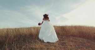 Rinnande brud i fantastisk lång klänning till och med landskapet stock video