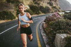 Rinnande det fria för kvinnlig idrottsman nen på huvudvägen royaltyfri fotografi