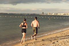Rinnande det fria för par på stranden Royaltyfri Foto