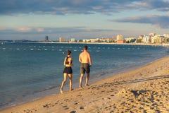 Rinnande det fria för par på stranden Arkivfoton