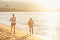 Rinnande det fria för par på stranden Fotografering för Bildbyråer