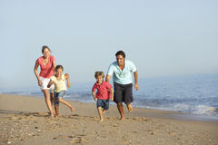 Rinnande familj på strandferie Royaltyfri Bild