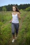 Rinnande flicka på grönt gräs Arkivbild