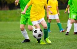 Rinnande fotbollfotbollspelare med bollen Fotbollsspelare som sparkar fotbollsmatchen på graden Arkivfoto