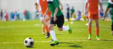 Rinnande fotbollfotbollsspelare Fotbollsspelare som sparkar fotbollsmatchen; Unga fotbollspelare som kör bollen arkivfoto