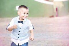 Rinnande gyckel för barn, med den himla- klänningen royaltyfri foto