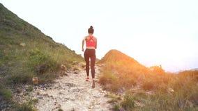 Rinnande kvinna på bergvägen Sportflicka som övar utanför i berg royaltyfria bilder