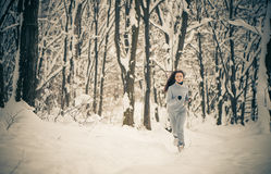 Rinnande kvinna på vinterskogen Royaltyfri Fotografi