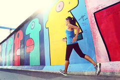 Rinnande kvinna som joggar vid Berlin Wall, Tyskland Royaltyfri Fotografi