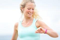 Rinnande kvinna som ser klockan för bildskärm för hjärtahastighet Arkivbild
